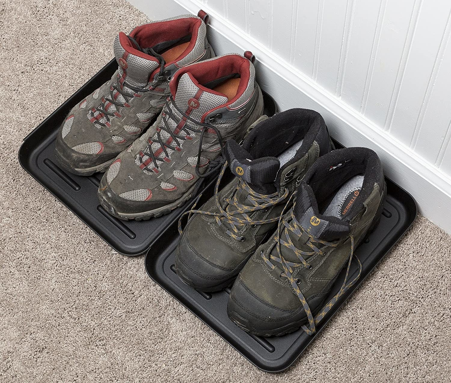 Two pairs of boots sitting in two small shoe trays