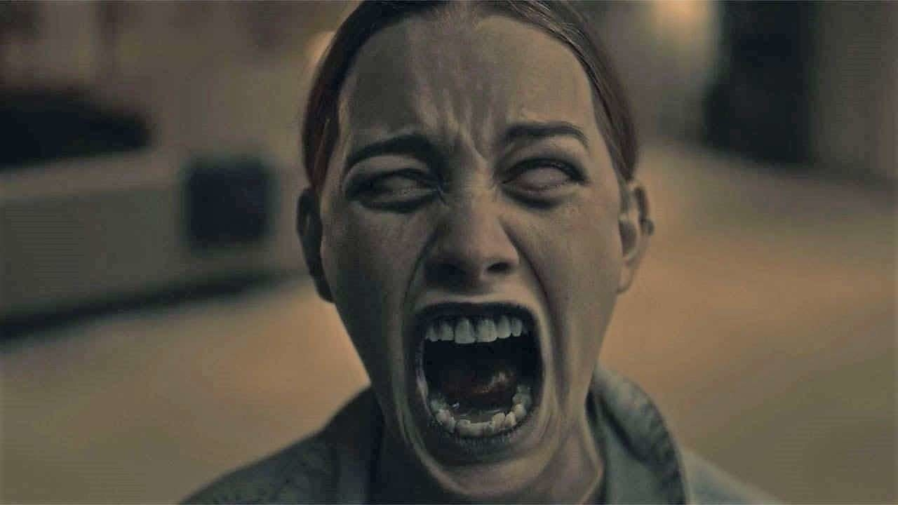 A woman with white eyes is screaming. Her teeth are all showing and her mouth is wide open