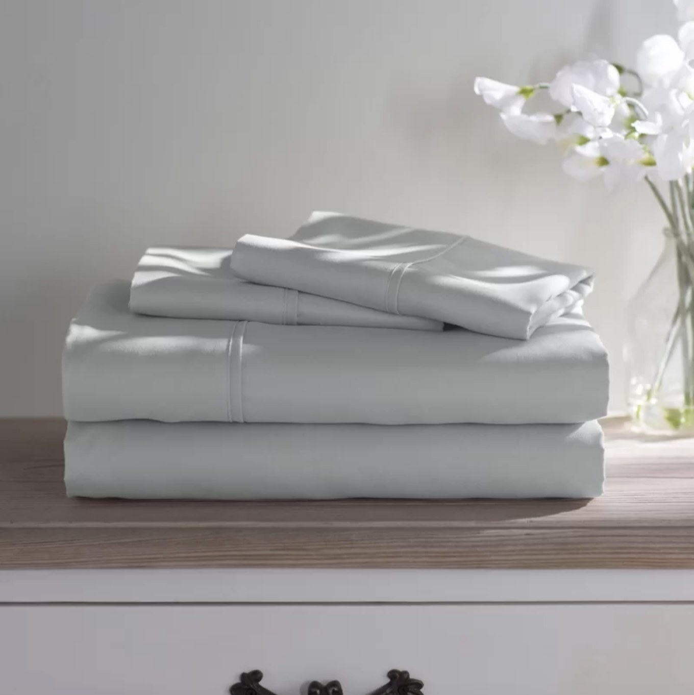 The sheet set in light gray sitting on top of a wood dresser