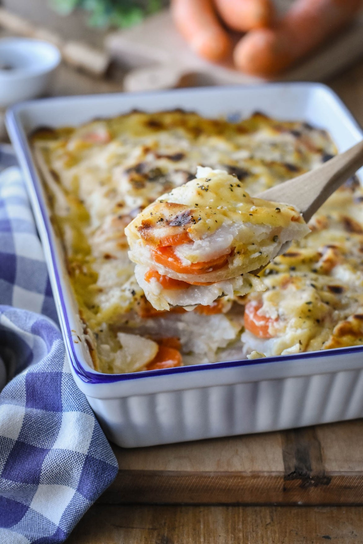 A baking dish filled with cheesy turnip and carrot au gratin.