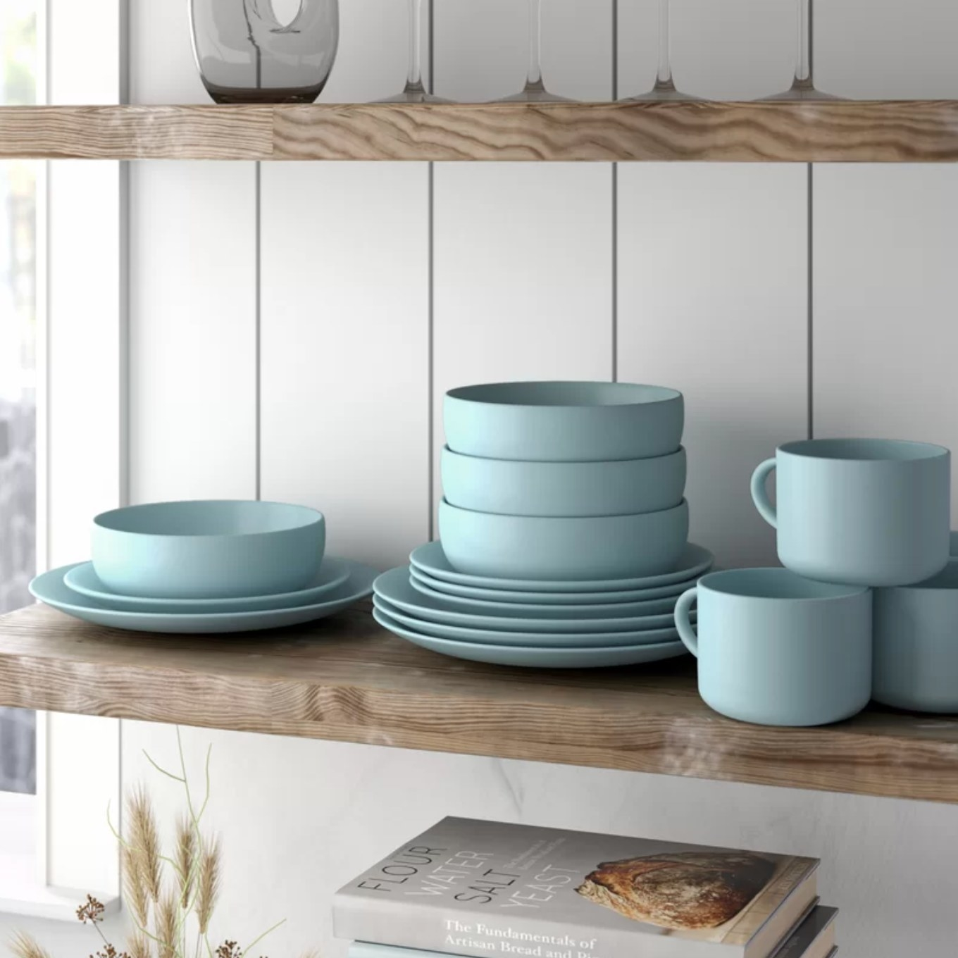 The dinnerware set on a wood shelf in a kitchen