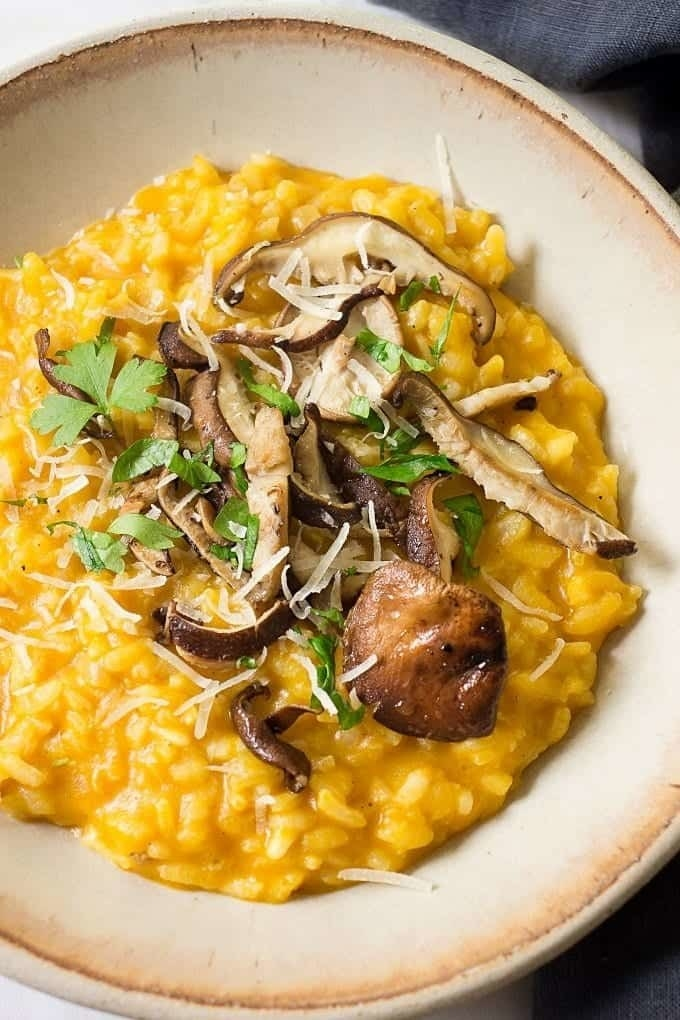 A bowl of pumpkin risotto topped with roasted sliced mushrooms, Parmesan cheese, and fresh herbs.