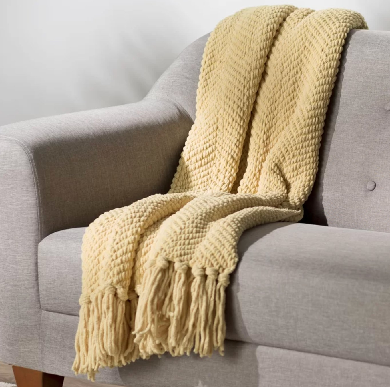 The knit blanket in jojoba yellow draped over a gray couch