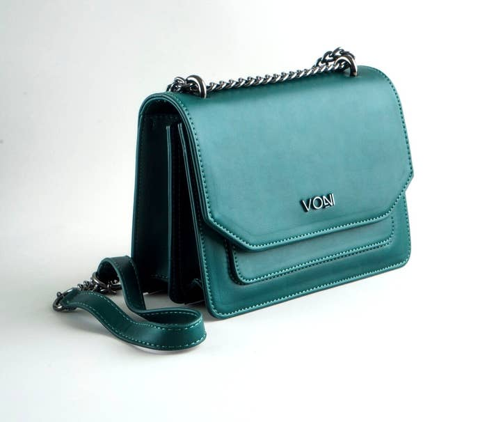 The rectangle-shaped handbag with a silver metal chain strap with a soft part in the center and a front flap, two inner compartments, and front-slip pocket.