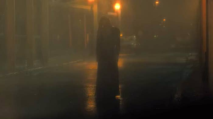 The silhouette of a woman in a long dress and long hair is visible in a rainy alleyway