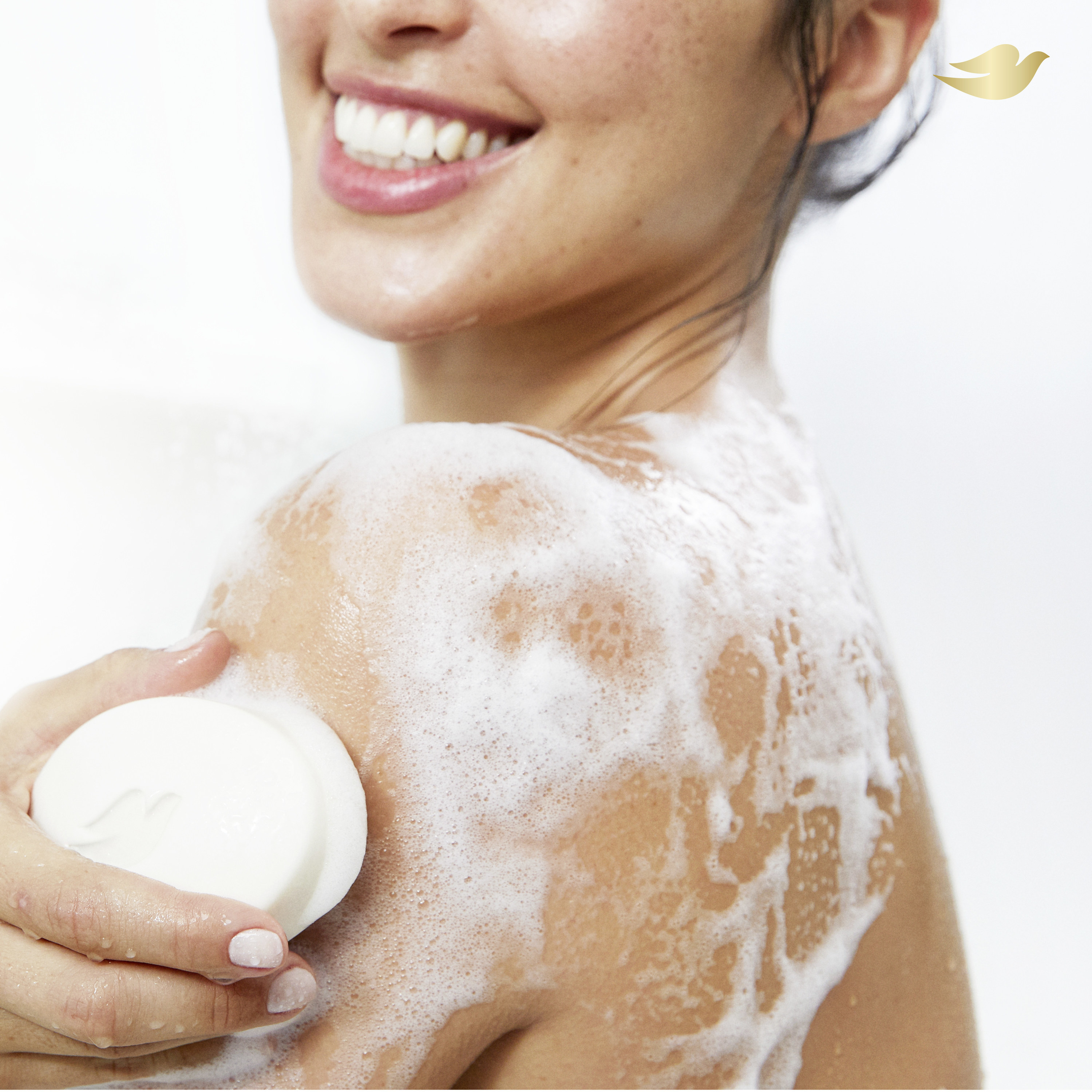 Woman using Dove white bar of soap in the shower with suds on her body