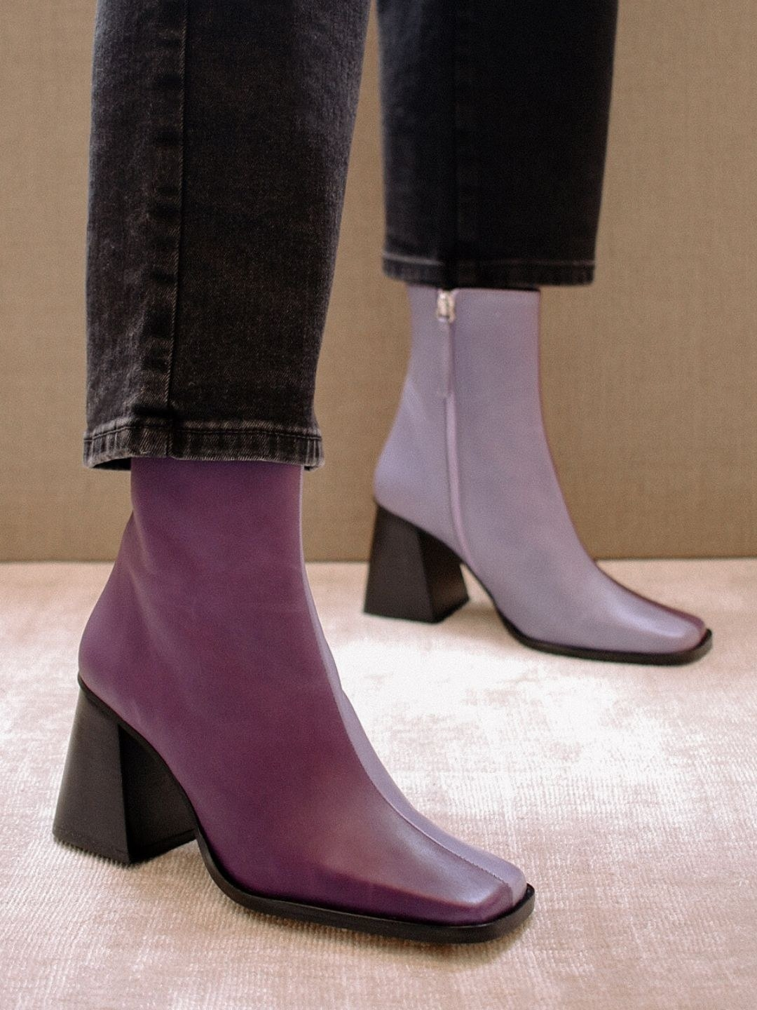 Model wearing the boots with one half lilac purple and the other a darker purples, with a dark brown chunky heel that gets wider as it gets closer to the ground.