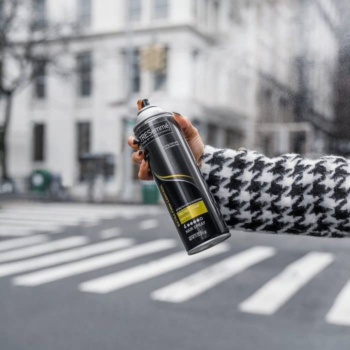 Person holding Tresemme hairspray in the middle of the road