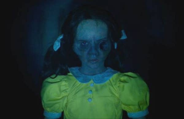 A girl with two pigtails is staring at the camera while wearing a dress with buttons and a peter pan collar
