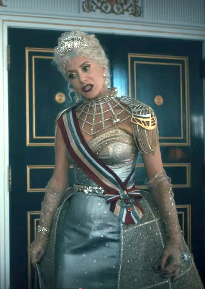 sparkly ballgown with princess waist with jeweled belt, a sheer sparkly cage over part of the skirt, a spiderweb-like jewel necklace from the neck to the chest, a metal shoulderpiece, sheer sparkly gloves, and a striped sash