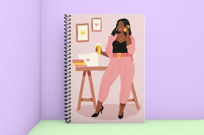 The notebook with an illustration of a Black woman in a pink suit on the phone, holding coffee, and standing in front of her cute desk