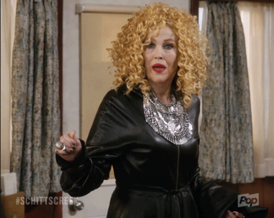 curly wig, black leather dress with long sleeves, a bib-like necklace, and pleated skirt after an empire waist