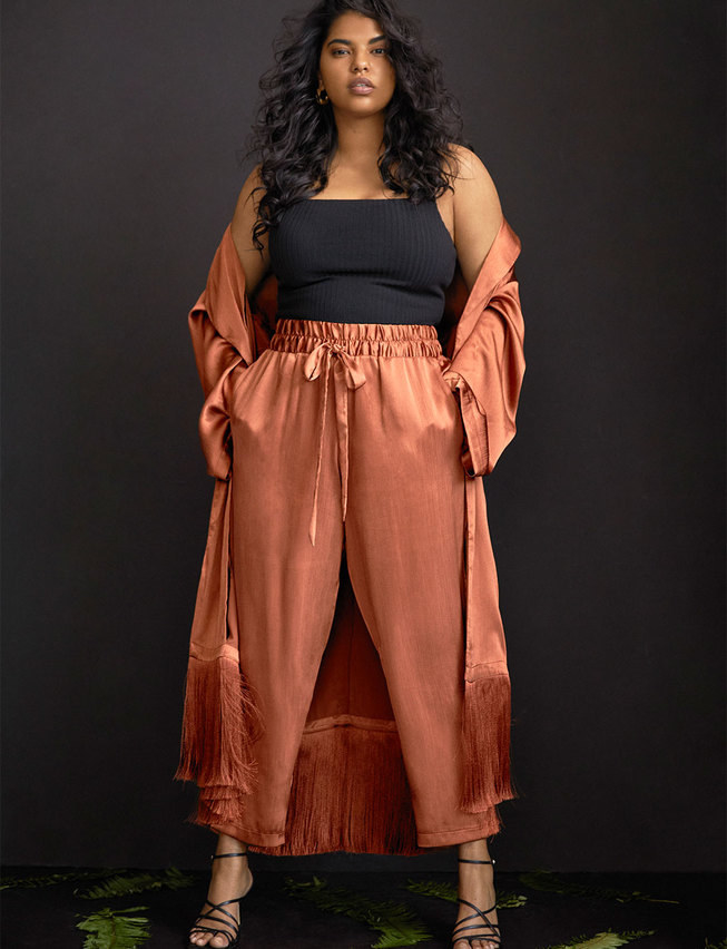 Model wearing the stain ankle-length pants with a thick elastic waist band, tie, and pockets on the side.