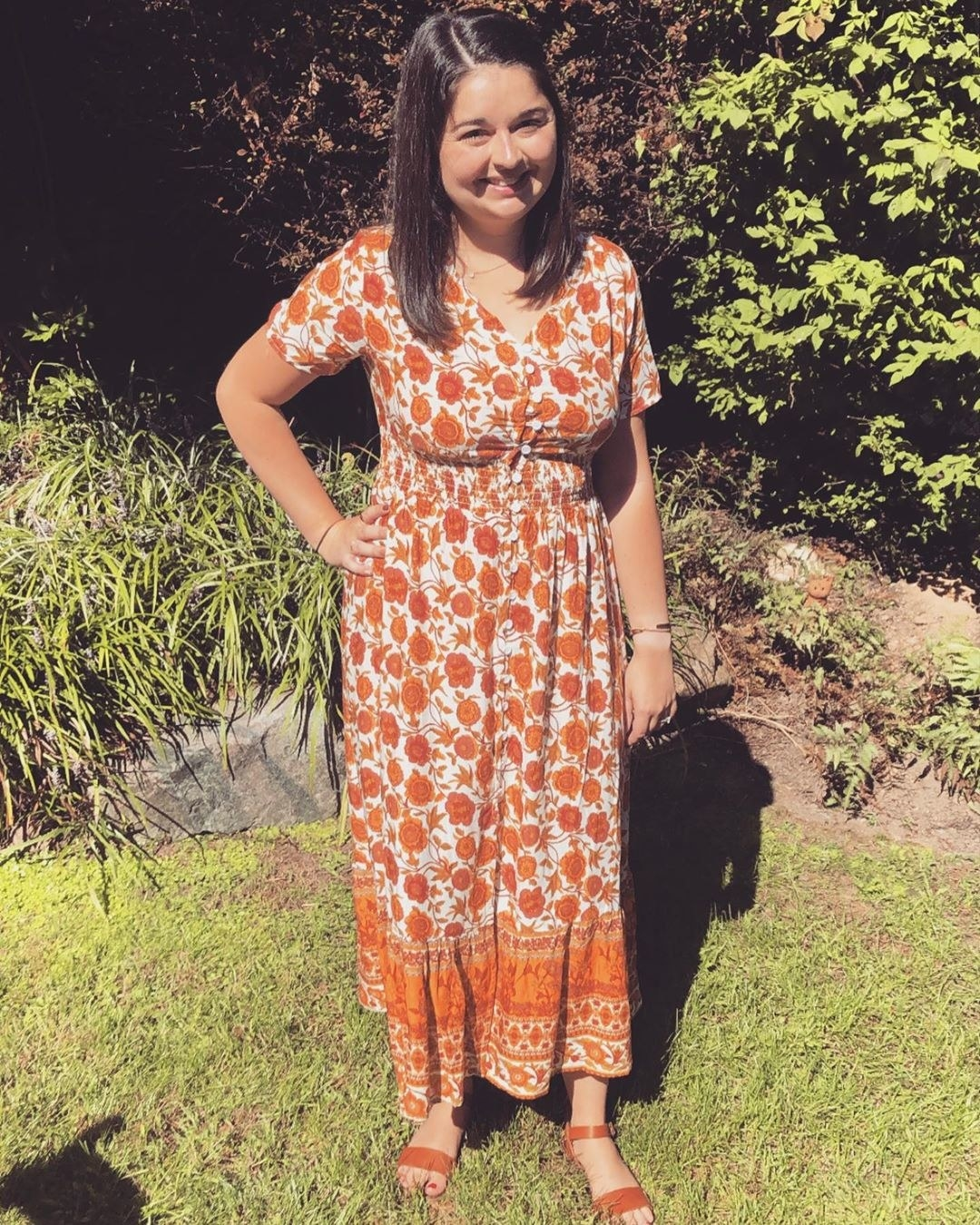 buzzfeed editor wearing a button-up orange midi dress with a floral pattern