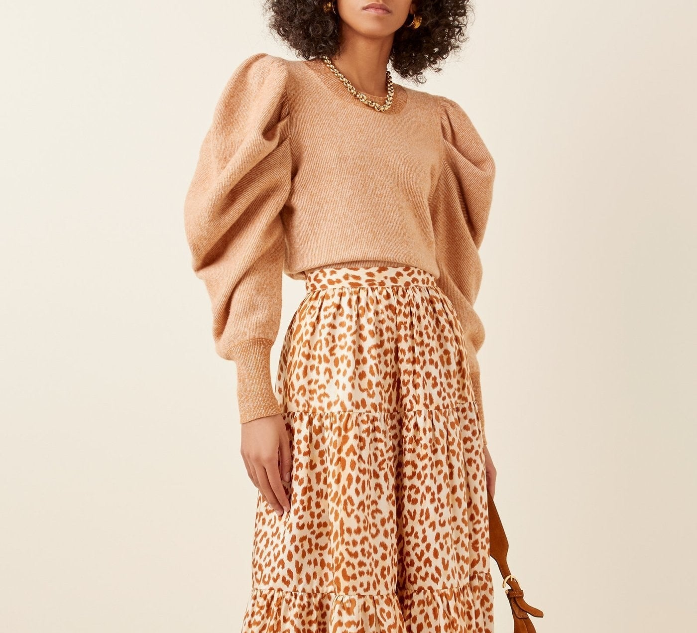 Model wearing the crewneck sweater with exaggerated puff-sleeves in tan with darker tan trim on the sleeves and neckline.