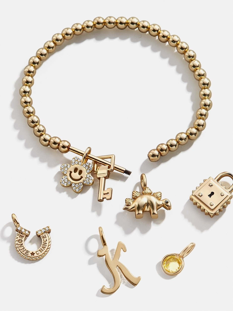 a gold beaded bracelet with a bar to hang various charms on