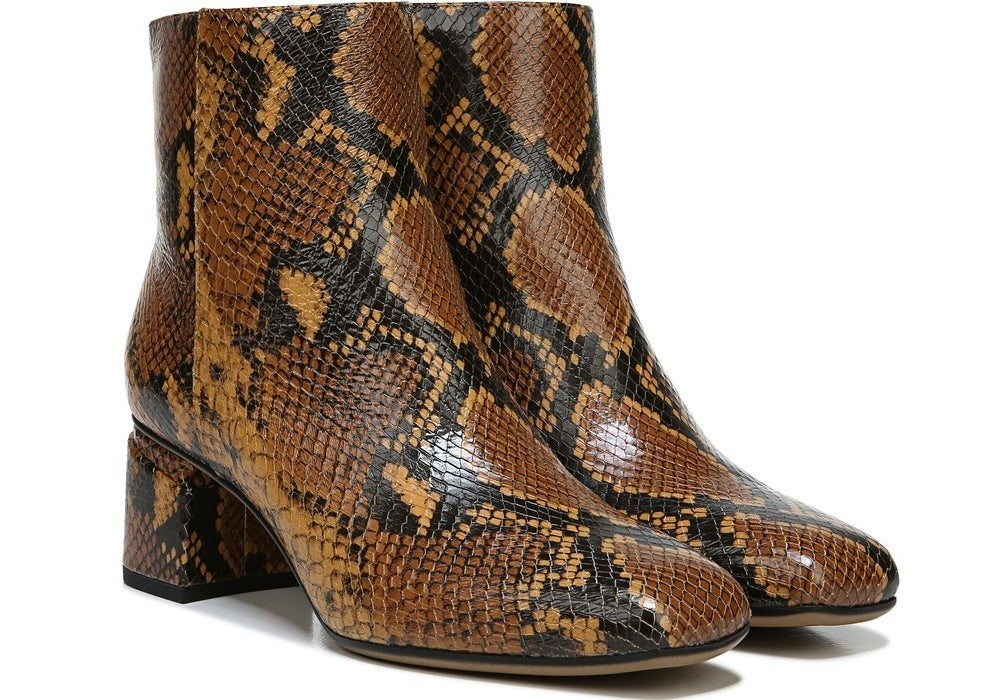 The ankle-length boots with a rounded toe and slightly chunky heel with a brown, black, and tan snakeskin print all over them.