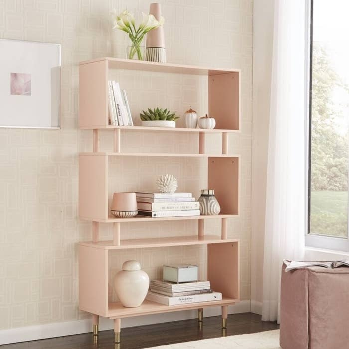 a pink bookshelf with three big shelves, two smaller shelves between them, and gold legs
