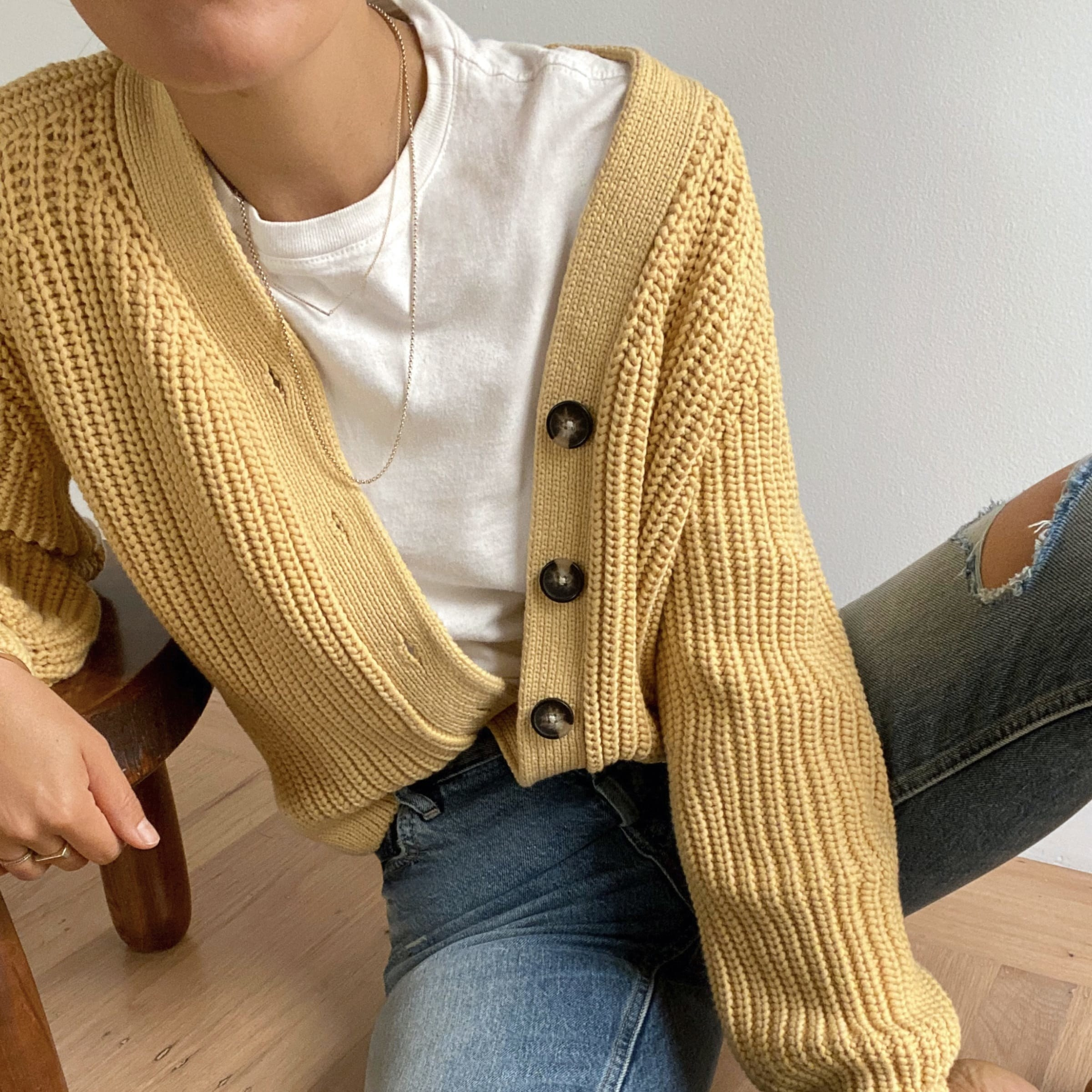 Model wearing the textured knit cardigan in yellow with brown buttons down the left side.