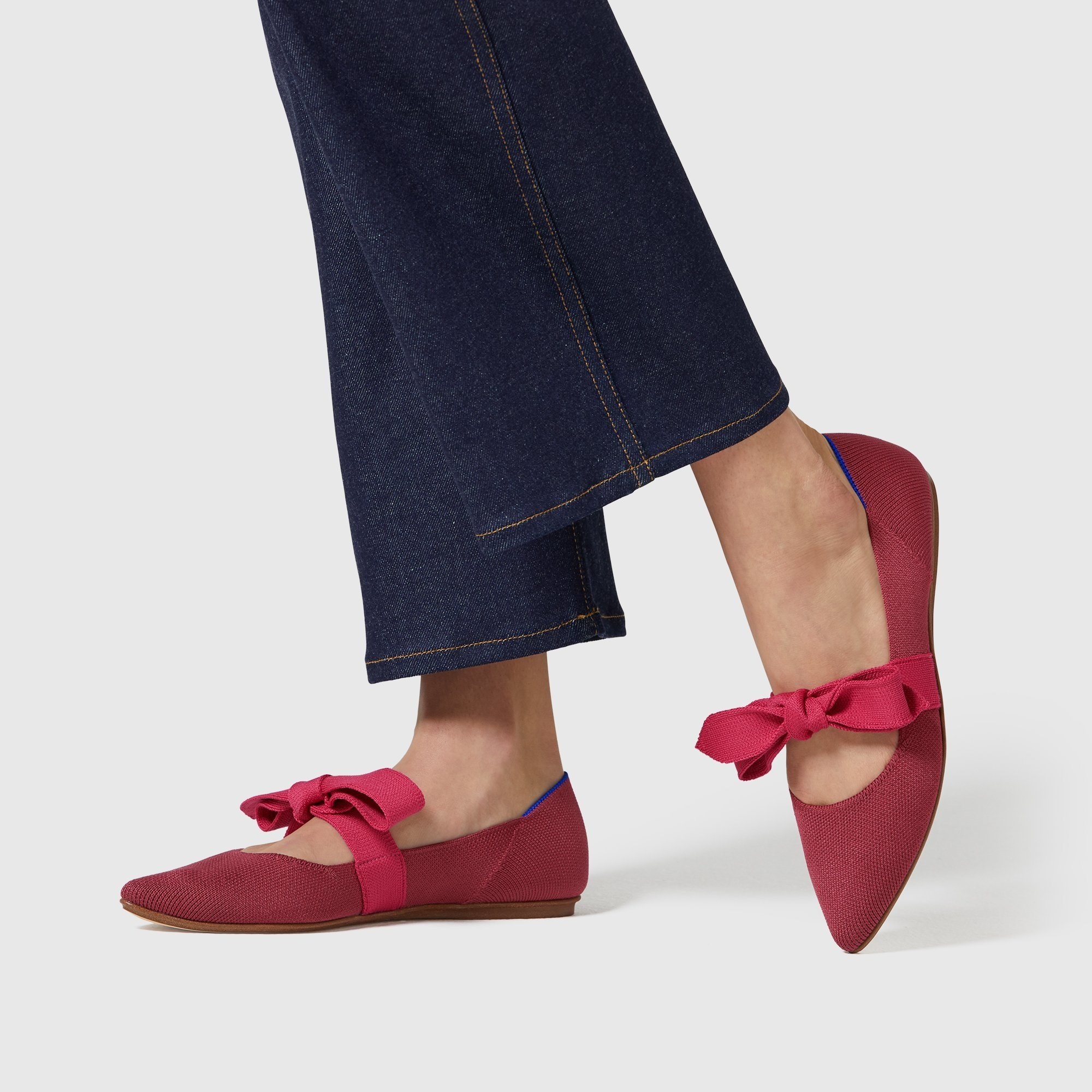 Model wearing the pointed-toe flats in red with a slightly lighter red boy tie across the top of the feet.
