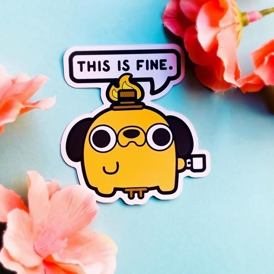 "The sticker shaped like a cute and round illustration of the dog with his hat on fire and the speech bubble that reads ""This is fine."""