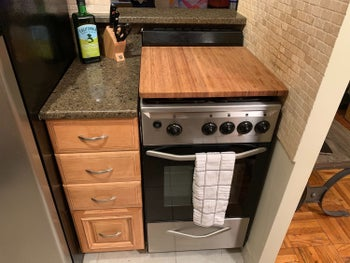 a kitchen stove with the bamboo burner cover on top creating more counter space