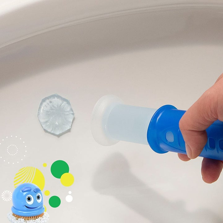 A hand stamping the circle of gel in the toilet