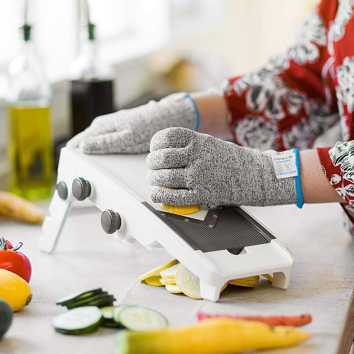 person wearing the gloves and using a mandolin cutter