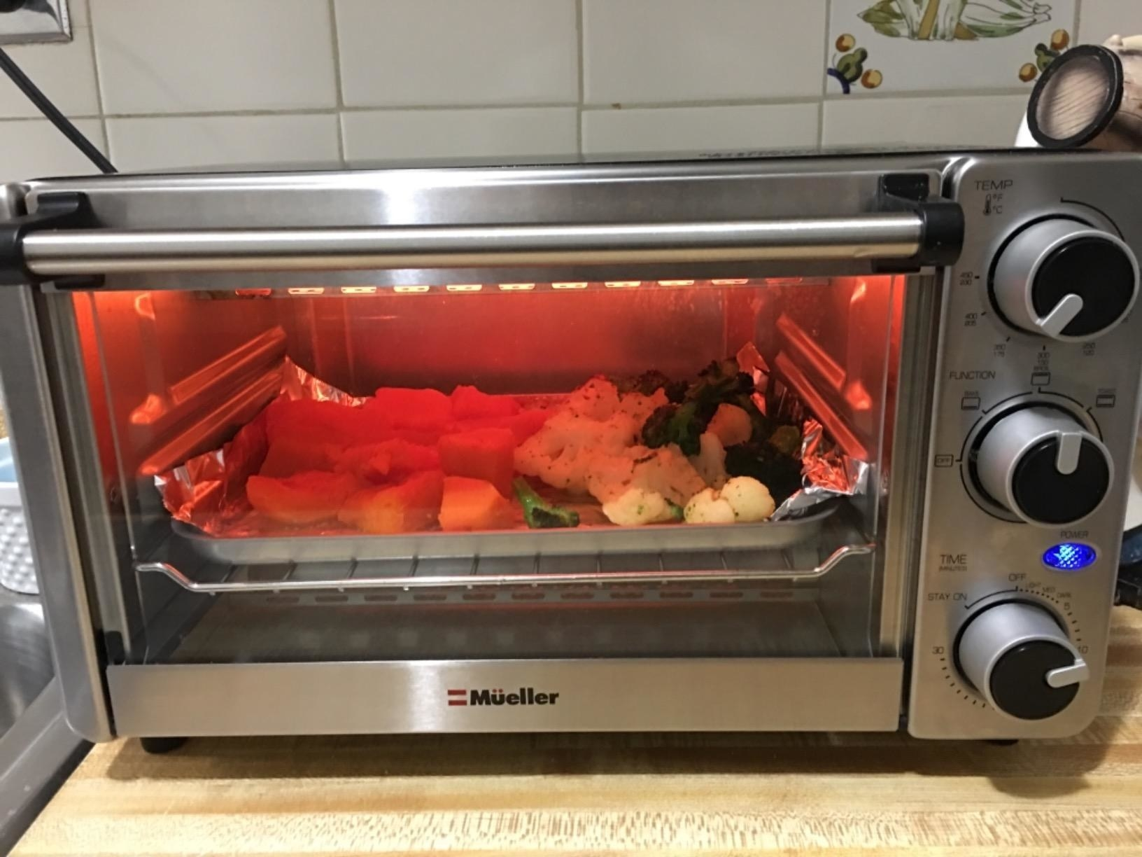 A reviewer image of some vegetables cooking inside the toaster oven