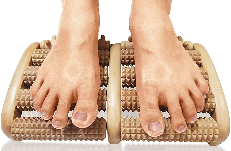 Two feet slide over a wooden foot massager