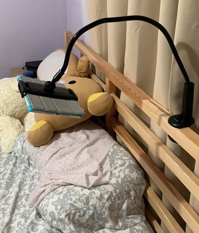 Reviewer photo of the stand in black clipped to the bedframe and holding an iPad above a pillow