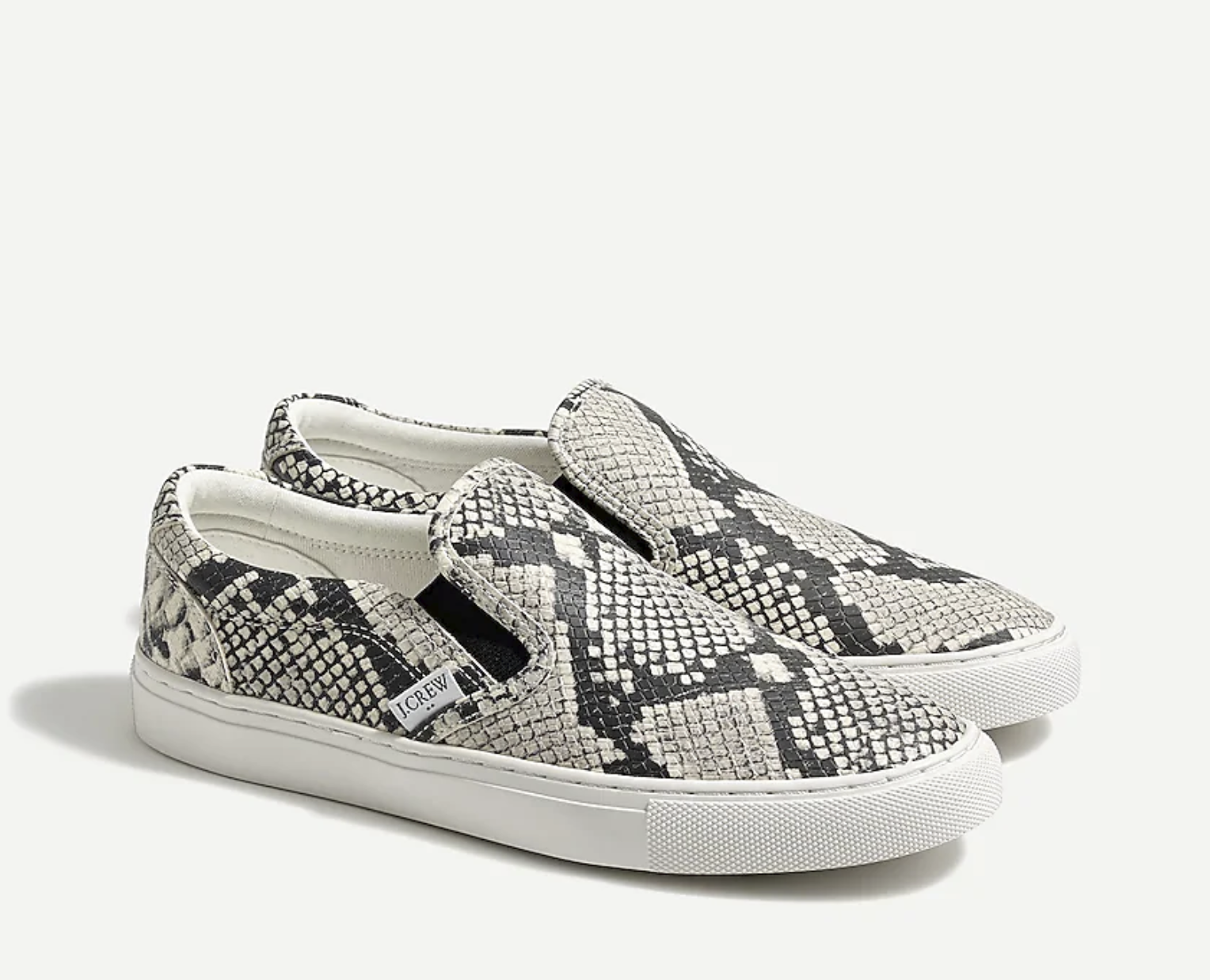 slip-on sneakers with a white and black snakeskin print and white sole
