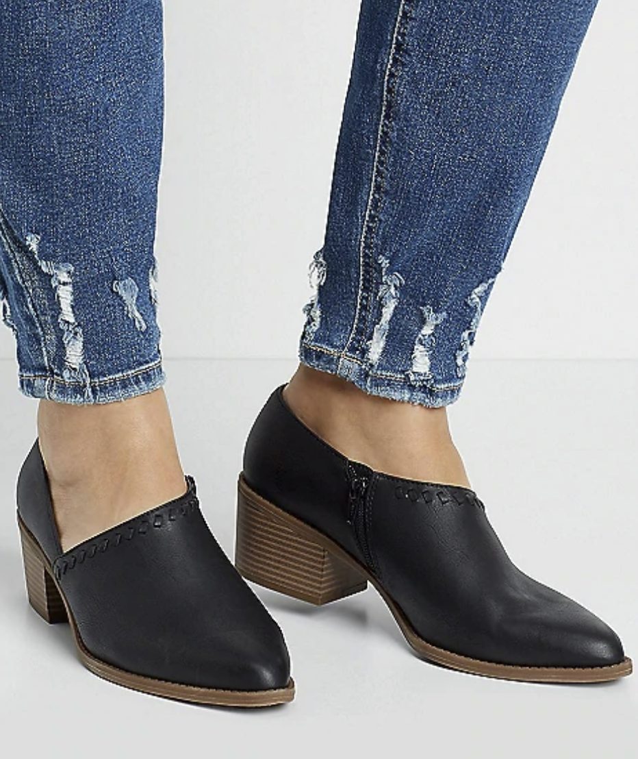 pointed toe leather show that comes up to just below the ankle with a side cutout on one side of the foot and stitching along the edge. it also has a brown sole and heel.