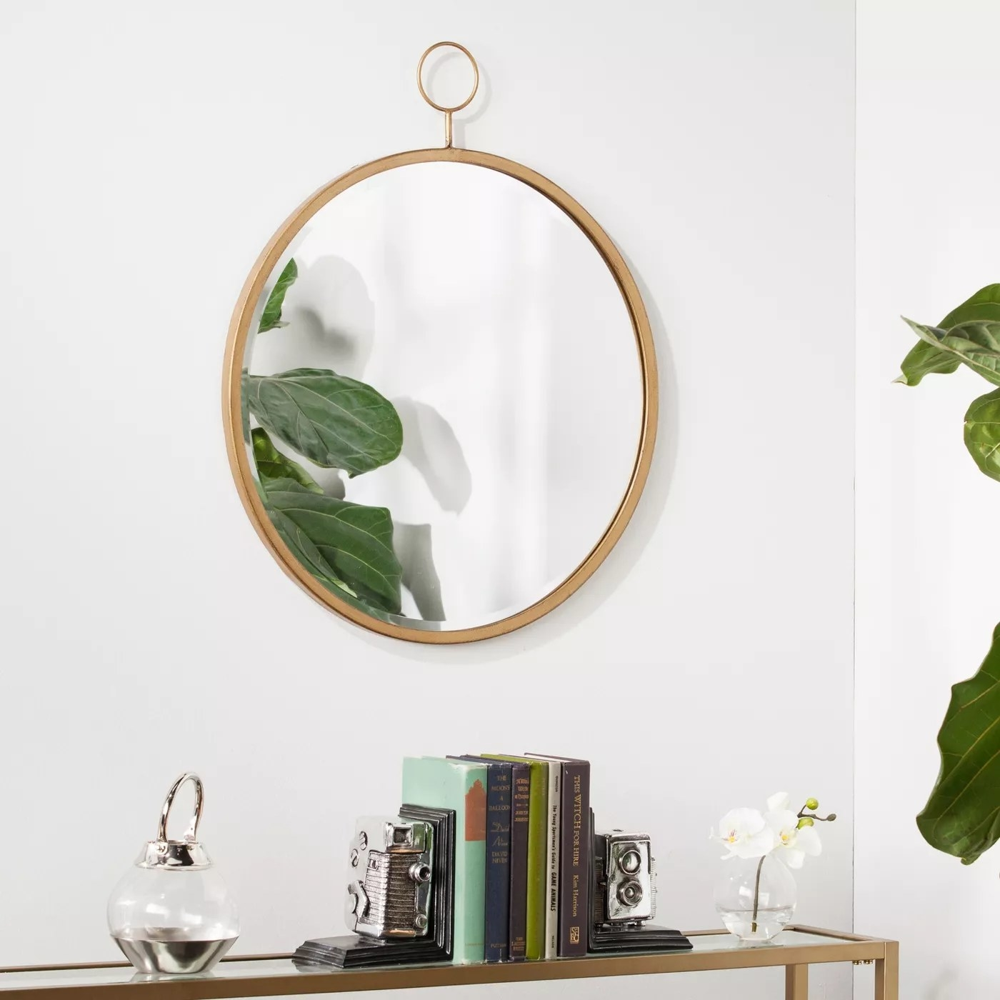 The round mirror with a beveled edge and a brass frame
