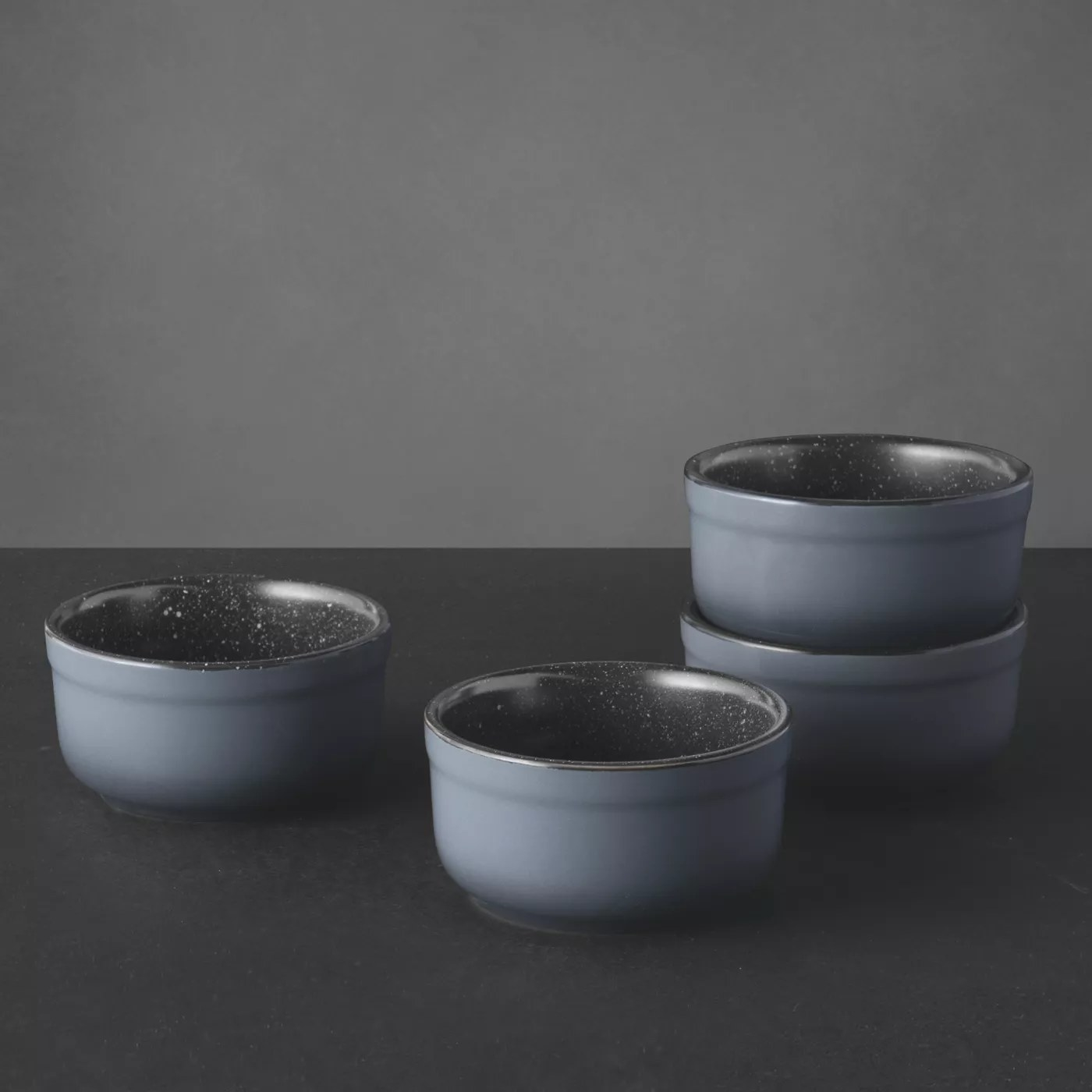 A set of four small, gray ramekins with speckled interiors