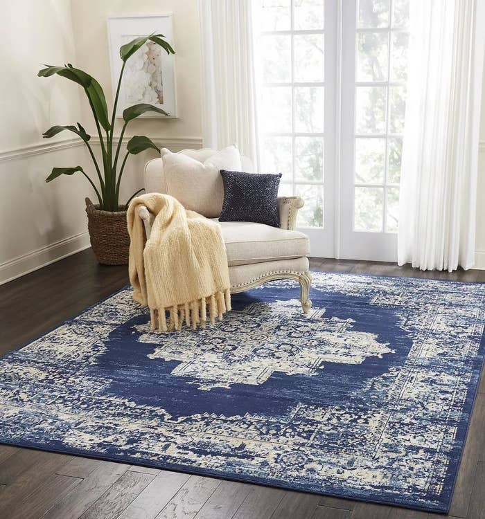 A navy and white area rug with a distressed Persian design