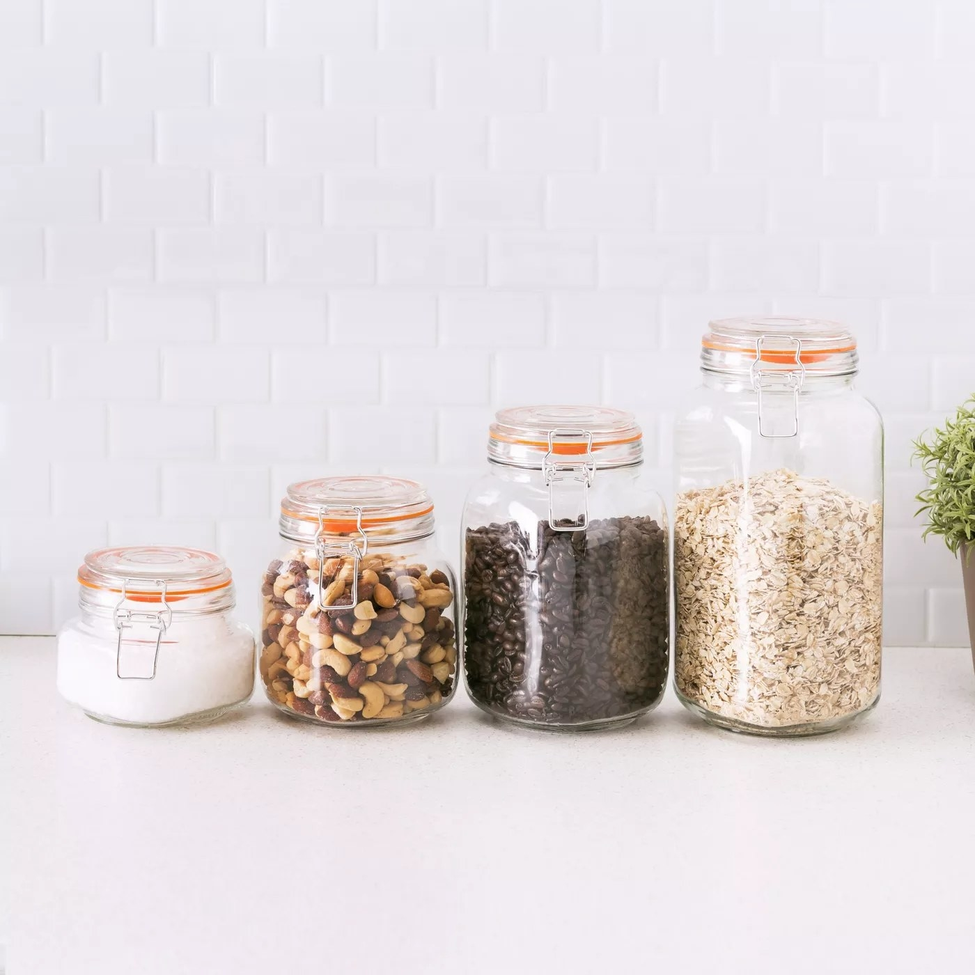 A set of glass canisters with metal clamps in sizes 14-oz, 27-oz, 47-oz, and 68-oz