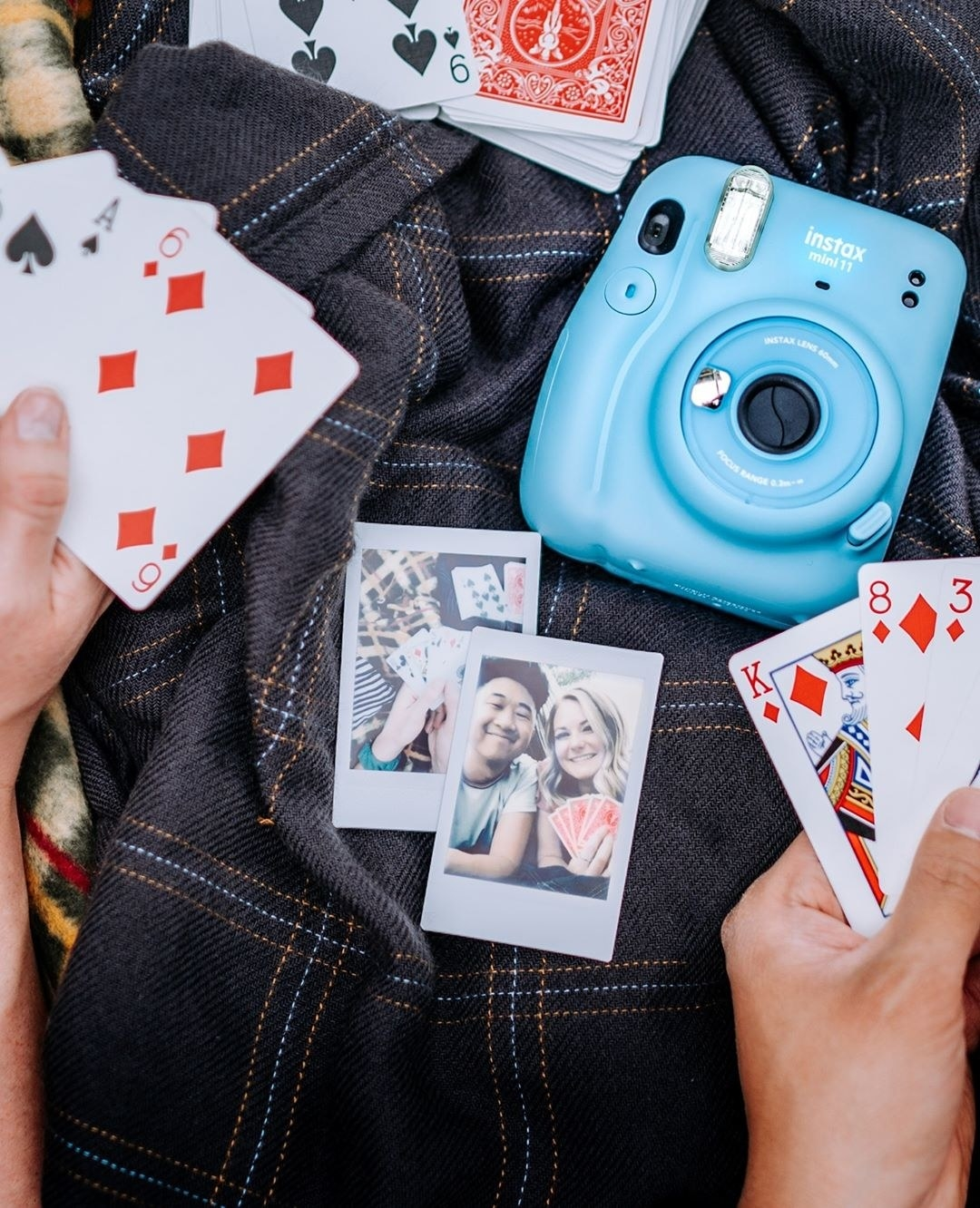 A Fujifilm camera on a cloth with two pictures and playing cards