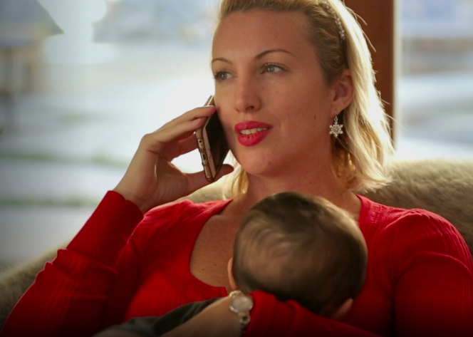 woman talking on her cell phone while holding a baby