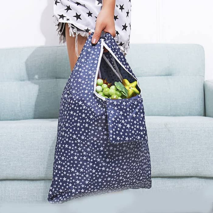 A person carrying a large reusable bag that's filled groceries