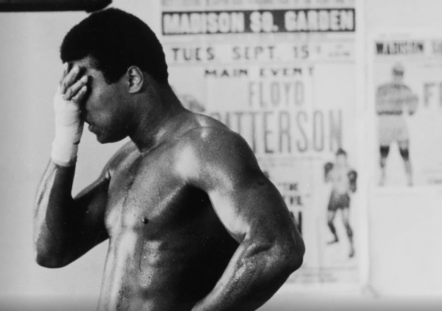 black and white photo of Muhammad Ali shirtless with his right hand on his forehead
