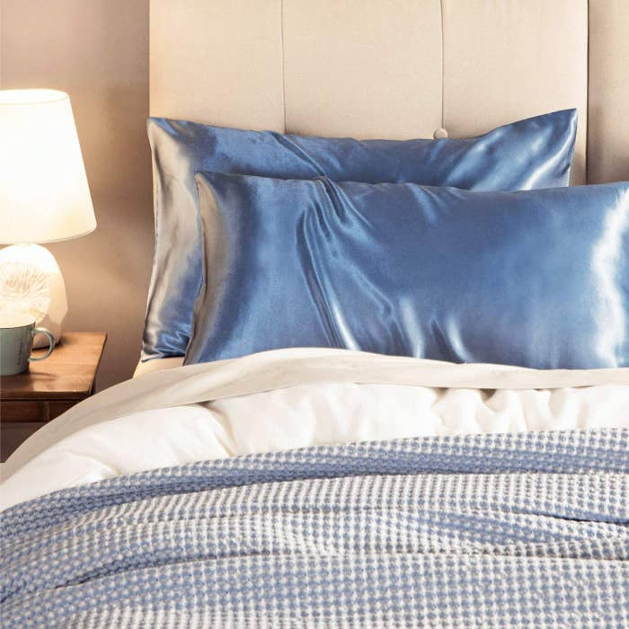 Two blue satin pillowcases on pillows and styled on a bed