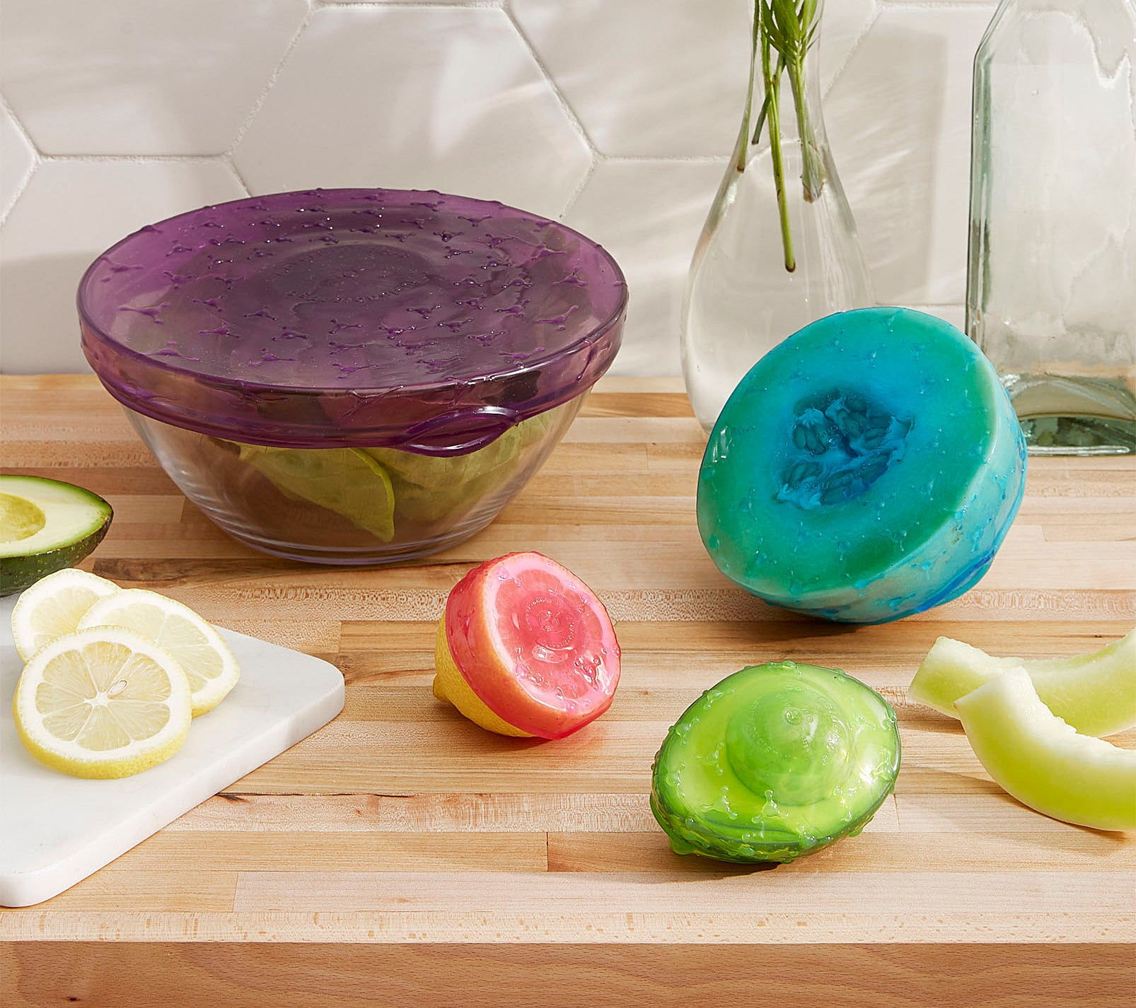 A large glass bowl, along with a half cut lemon, melon, and avocado are covered in a stretchy silicone cover