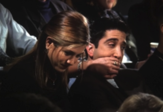 Rachel covering Ross's mouth with her hand