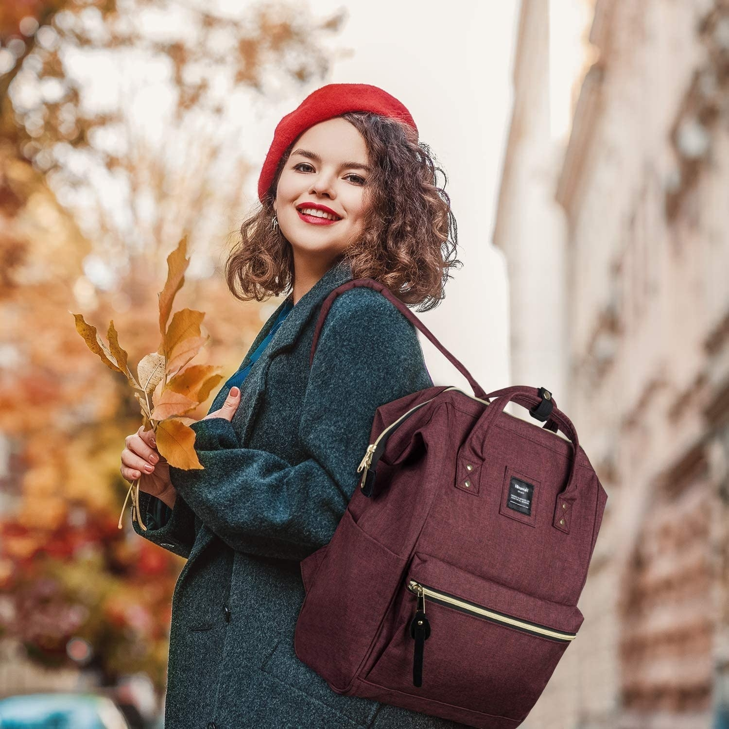 A smiling person wears the backpack while walking through a city street