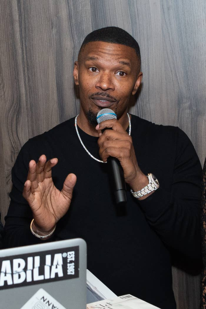 Jamie Foxx holding a microphone wearing a dark outfit