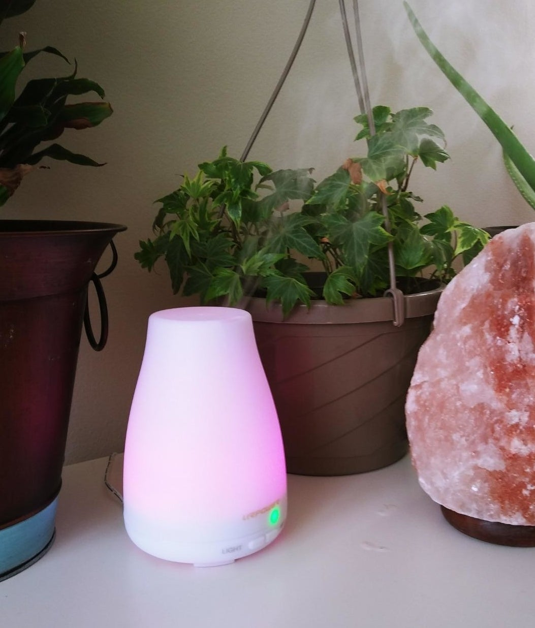 Reviewer pic of a small white diffuser lit up pink.