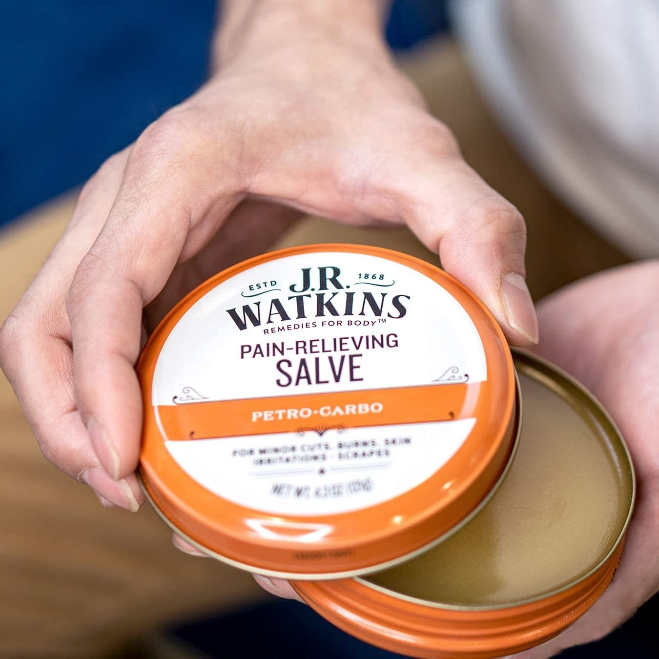 A close up of a person opening a tin of the salve