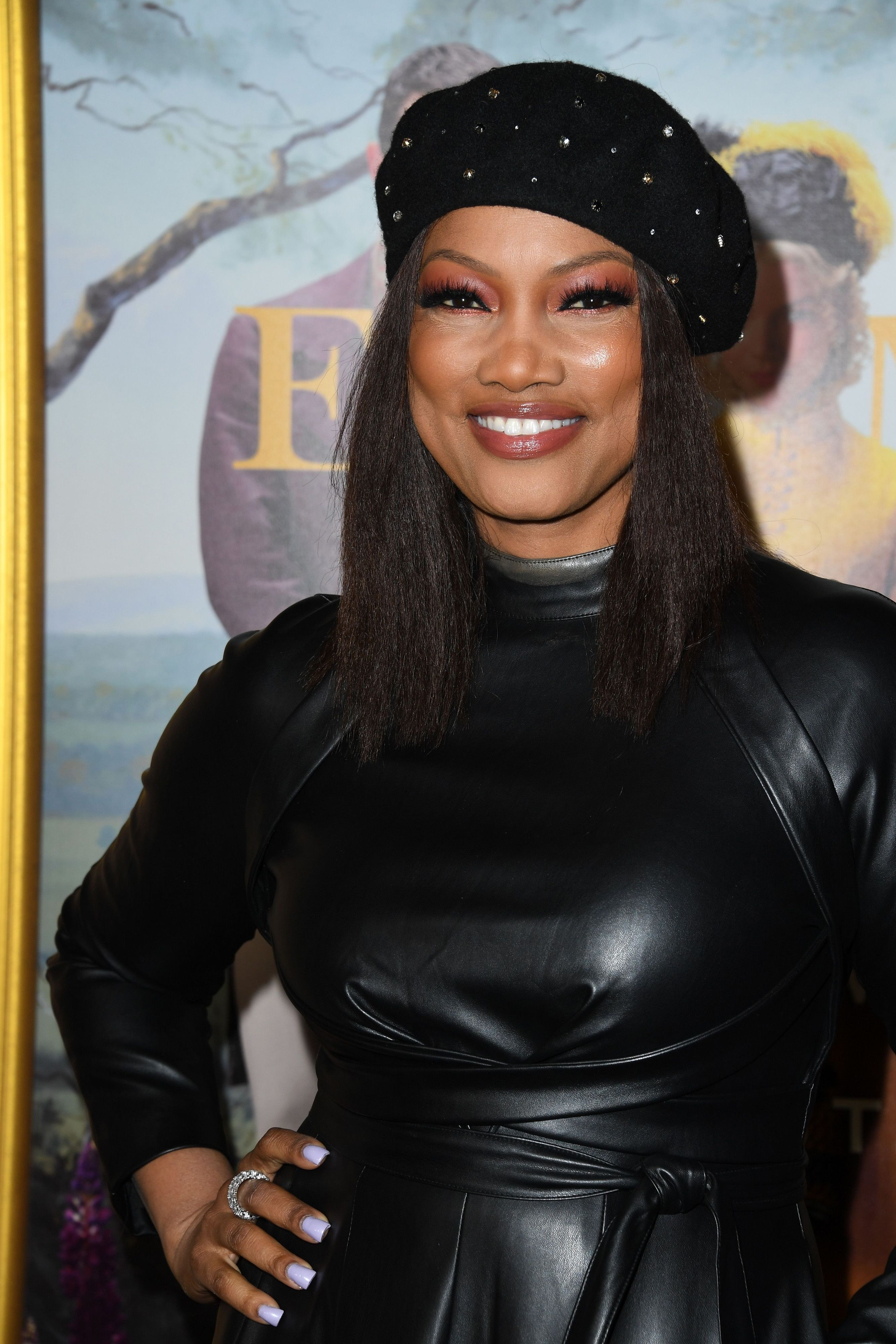 Garcelle posing with her hand on her hip wearing a dark leather outfit