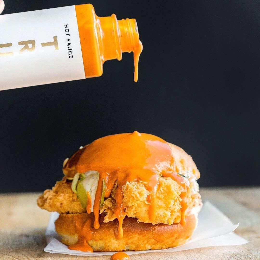 A close up of the hot sauce being poured onto a chicken sandwich